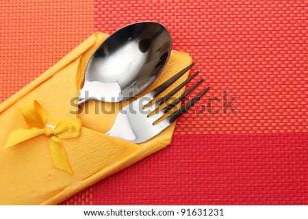 Fork and spoon in a yellow cloth with a bow on a red tablecloth - stock photo