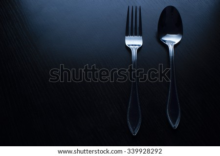 fork and spoon on a black table dark tone - stock photo