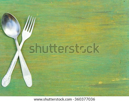 Fork and spoon on old wooden table. Vintage texture, background. Menu. - stock photo