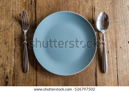 Fork and spoon on plate with wooden table background
