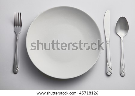 fork and spoon on the side of kitchen plate - stock photo