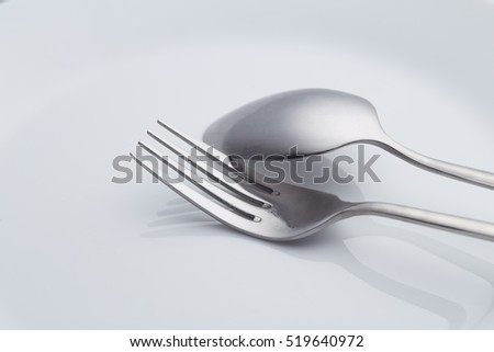 Fork and Spoon on white dish luxury