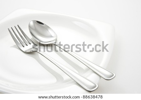 Fork and Spoon on white plate - stock photo