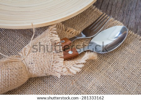 Fork and spoon with plate on wooden dining tables - stock photo
