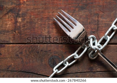 Fork attached with metal chain on wooden background - stock photo