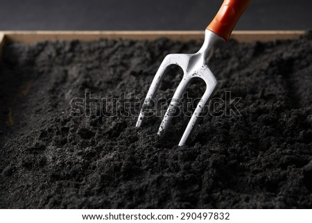 Fork digging on soil,close up - stock photo