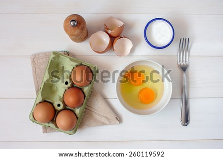 Fork for whipping eggs and raw eggs in a bowl on a white wooden table - stock photo