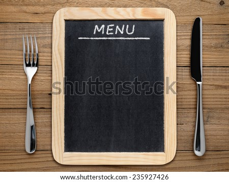 Fork, knife and blackboard menu on wooden background - stock photo