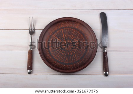 Fork, knife and dinner plate  on a light wood background - stock photo
