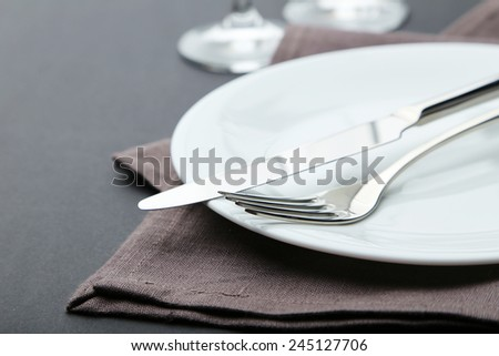 Fork, knife and plate on black background - stock photo