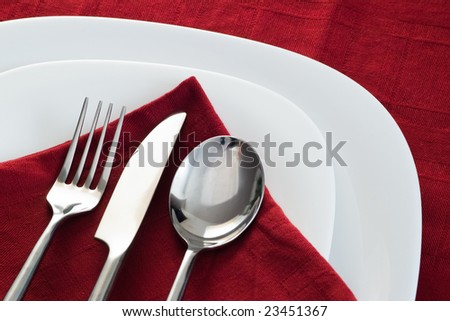 fork knife and spoon on white plate and dark red napkin - stock photo
