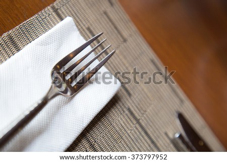 Fork resting on a napkin. Arranged on a table in a restaurant. - stock photo