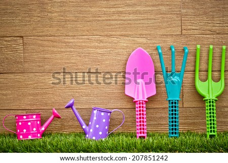 fork, shovel and rake on green grass with wood background - colorful gardening tools - stock photo