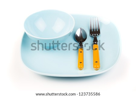 Fork, spoon and plate on white