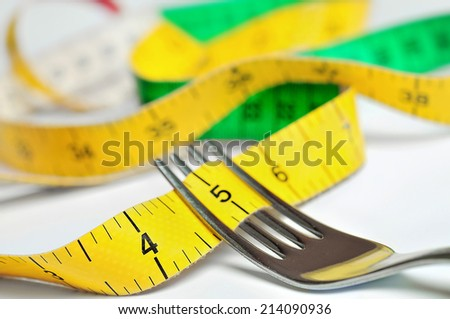Fork with centimeter on table - stock photo