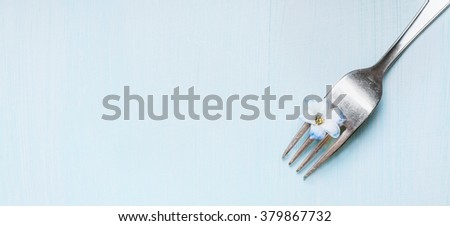 Fork with little blue flower on light green shabby  rustic background, top view, banner. - stock photo