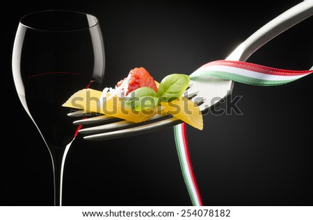 fork with macaroni tomato sauce and glass of red wine on dark background - stock photo