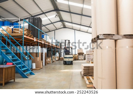 Forklift amid rows of boxes in a large warehouse - stock photo