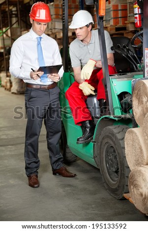 Forklift driver and supervisor working in warehouse - stock photo