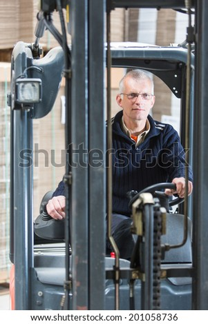Forklift driver, manning the controls and steering wheel of his forklift in a large warehouse. Just in Time concept - stock photo