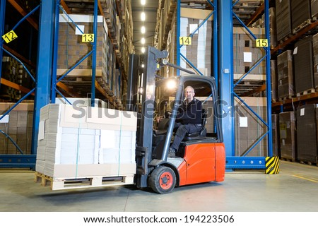 Forklift driver posing in front of a row with storage racks. On his fork he is transporting a pallet full of flat cardboard boxes. - stock photo