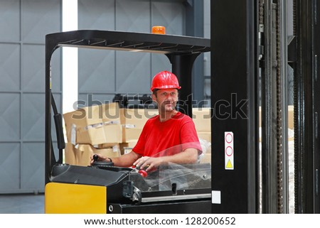 Forklift driver with red helmet  in distribution warehouse - stock photo