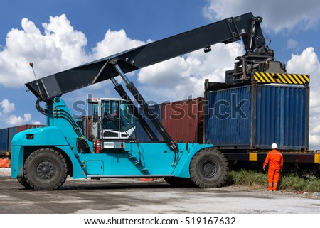 Forklift handling container box loading at the Docks with cloudy sky