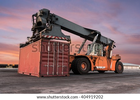 Forklift handling container box loading the Docks with Truck at sunset - stock photo