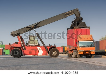 forklift handling container loading box from freight train to the truck - stock photo