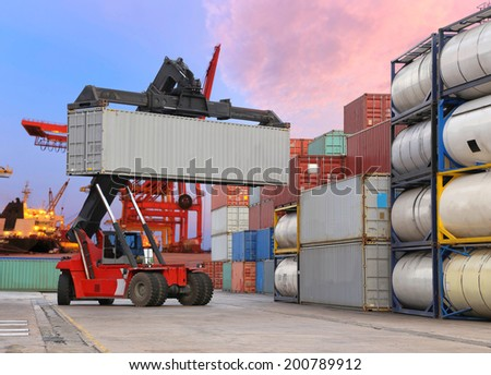 forklift handling the container box at dockyard with harbour background - stock photo