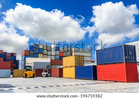 Forklift handling the container box with blue sky - stock photo