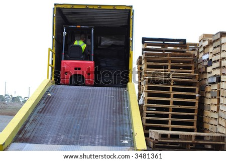 Forklift in backed of truck - stock photo