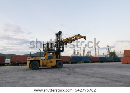 Forklift is waiting handling container box at train station near petrochemical plant
