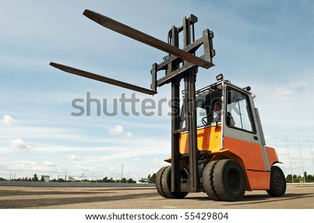 Forklift loader for warehouse works outdoors with risen forks