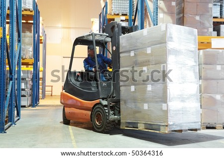 Forklift loader moving at warehouse with a cardboard boxes - stock photo