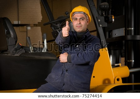 Forklift operator giving okay sign at warehouse - a series of METAL INDUSTRY images. - stock photo