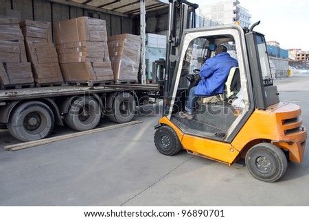 Forklift operator loading on a truck. - stock photo