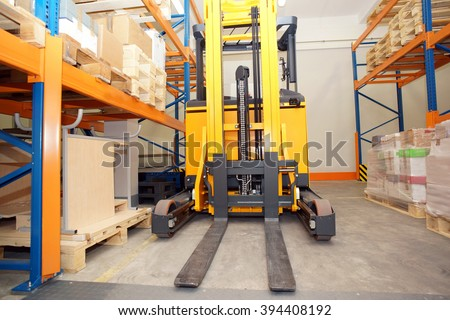 forklift, Shelves and racks with pallets in distribution warehouse interior - stock photo