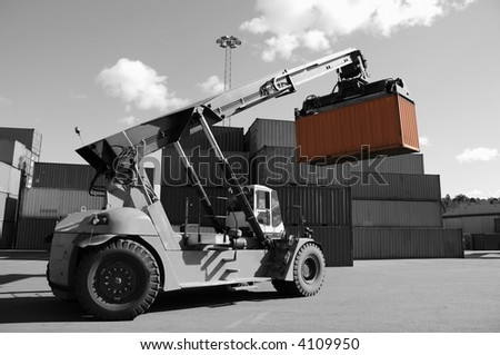 forklift stacking containers in port, dual color concept in black/white and orange - stock photo