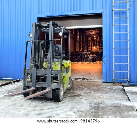 Forklift standing at the entrance of a large modern warehouse - stock photo
