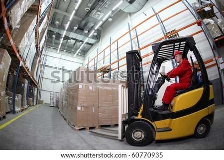 forklift  truck reloading pallets in storehouse - stock photo