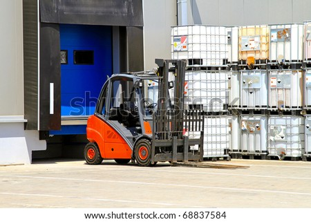 Forklift vehicle in front of distribution warehouse