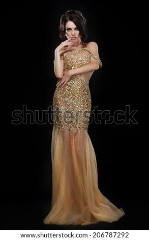 Formal Party. Glamorous Fashion Model in Elegant Golden Dress over Black - stock photo