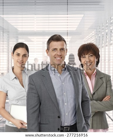 Formal portrait of group of happy business people at office, businessman leading.