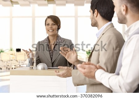 Formal speech at pulpit on business conference presented by successful businesswoman, colleagues clapping. - stock photo