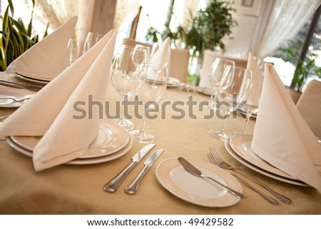 Formal Table setting in a restaurant focus on the glasses in front - stock photo