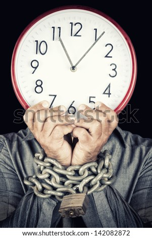 Formally dressed man holding a clock in place of his face with his hands chained with a metallic chain and padlock (useful to illustrate overworked  or stressed people) (isolated on white) - stock photo