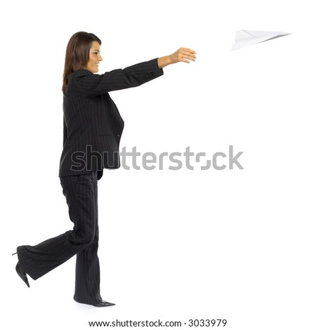 Formalwear woman's throwing toy paper plane. Side wiev. Whole body is visable.