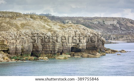 Former cliff quarries at Breston on the east side of the Isle of Portland with the Victorian prison in the far distance.  - stock photo