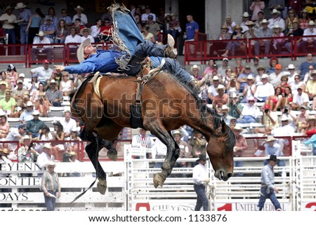 Former World Champion Bareback rider, Kelly Timberman, makes a successful ride at the 2005 Cheyenne Frontier Days rodeo (editorial). - stock photo